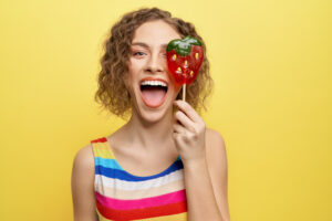 Happy, cheerful girl holding sweet red strawberry lollipop and having fun. Playful model in striped dress looking at camera, posing on yellow background.